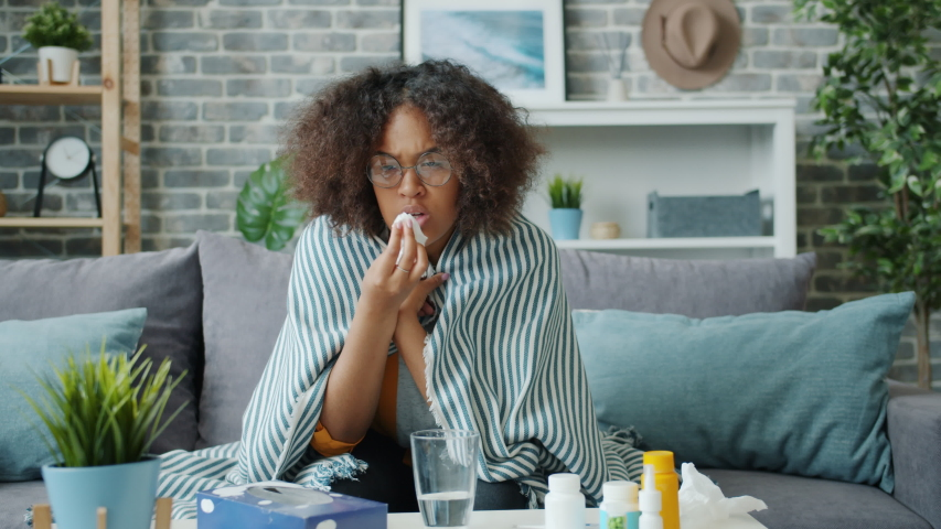 Unhappy young African American woman is coughing in paper tissue feeling sick at home on couch sitting alone covered with blanket. Lifestyle and health concept. | Shutterstock HD Video #1038994262