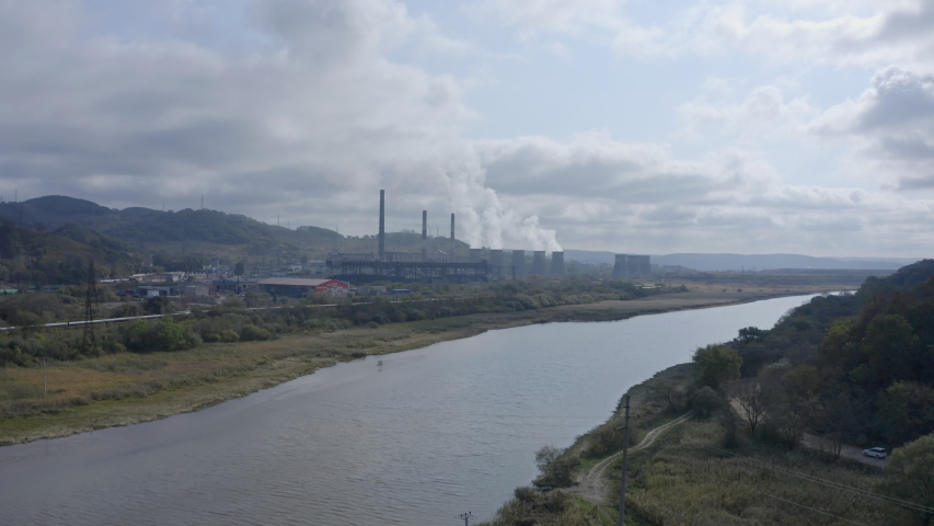 Landscape view with a coal-fired power station with its chimneys and funnels releasing white smoke into the air on a sunny and cloudy day. Aerial shot