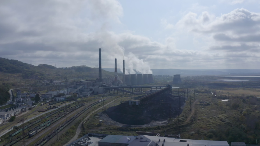 Slow push in shot of a coal-fired power station with its chimneys and funnels releasing white and grey smoke into the air on a sunny and cloudy day. Aerial shot