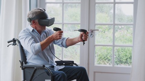 Senior Disabled Man In Wheelchair At Home Wearing Virtual Reality Headset Holding Gaming Controllers