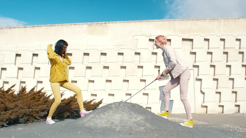 Two fashionable woman golfing with a real egg