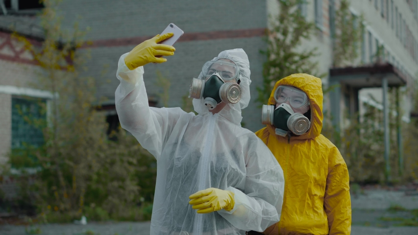 Two scientists put on a respirator and conduct research. The environment is in danger. Two girls in protective suits from radiation. Enter the data into the phone. Coronavirus pandemic, COVID-19. | Shutterstock HD Video #1039026296