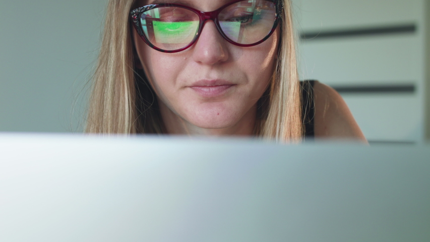 Busy girl in glasses working with laptop and smiling in office. Slowly in 4K | Shutterstock HD Video #1039026509