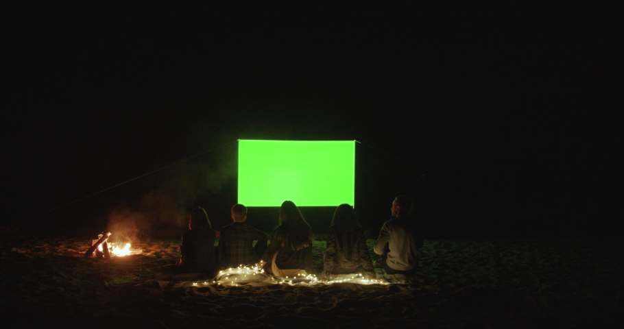 Outdoor cinema. Friends gather in a campfire camp and watch a movie with a projector on the beach near the sea. Green screen. A place for your image.