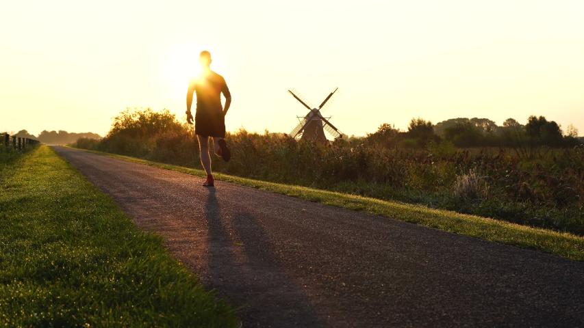 Man running in the Dutch countryside near a traditional windmill. Groningen, Holland. | Shutterstock HD Video #1039030613