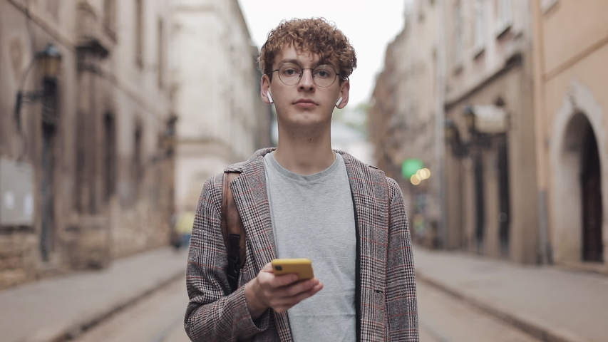 Close Up of Calm Millenial Hipster Guy in Earphones and Glasses Looking to Camera Holding Smartphone in his Hand Standing at Blured Old City Background Zoom.