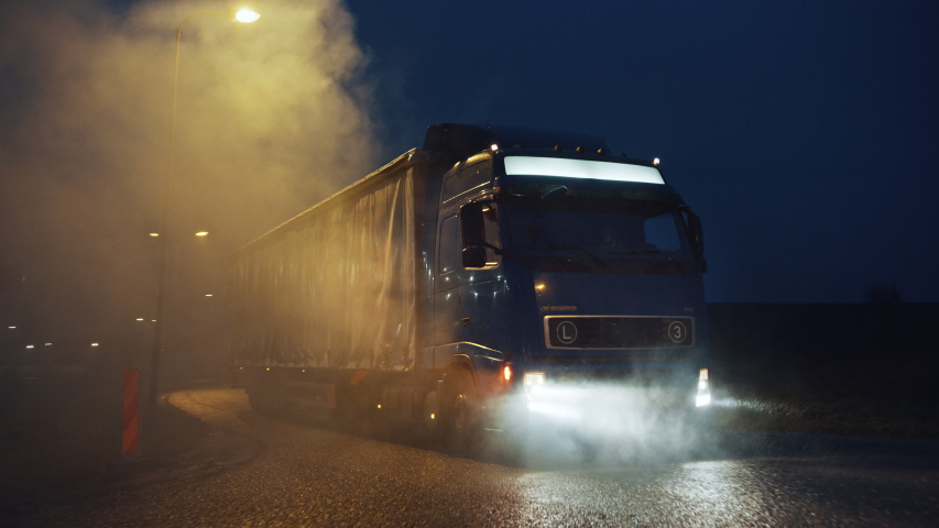 Blue Long Haul Semi-Truck with Cargo Trailer Full of Goods Travels At Night , Turning on the Freeway Road, Driving Across Continent Through Rain, Fog, Snow. Industrial Warehouses Area. Front Following