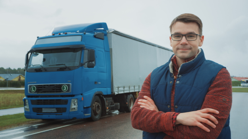 Professional Young Truck Driver Crosses Arms and Smiles. Behind Him Parked Blue Long Haul Semi-Truck with Cargo Trailer