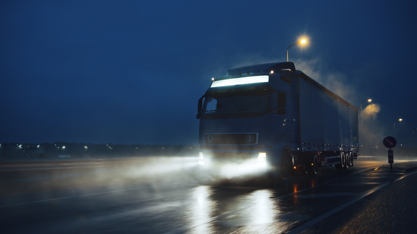 Blue Long Haul Semi-Truck with Cargo Trailer Full of Goods Travels At Night on the Freeway Road, Driving Across Continent Through Rain, Fog, Snow. Industrial Warehouses Area. Front Following Shot
