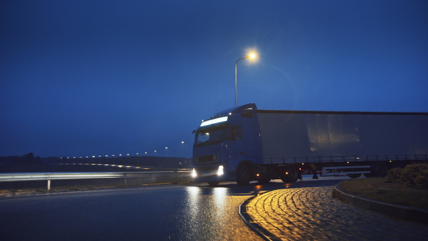 Blue Long Haul Semi-Truck with Cargo Trailer Full of Goods Travels At Night on the Freeway Road, Driving Across Continent Through Rain, Fog, Snow. Industrial Warehouses Area. Front Following Shot | Shutterstock HD Video #1039037258
