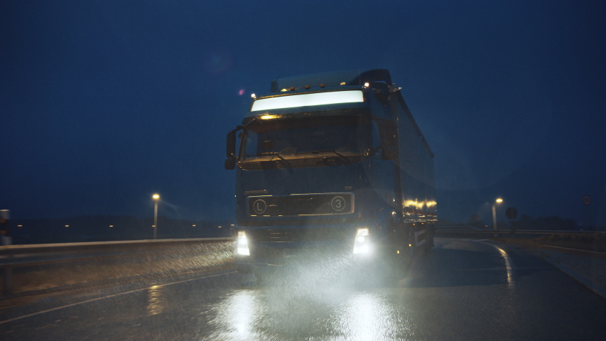 Blue Long Haul Semi-Truck with Cargo Trailer Full of Goods Travels At Night on the Freeway Road, Driving Across Continent Through Rain, Fog, Snow. Industrial Warehouses Area. Front Following Shot | Shutterstock HD Video #1039037261