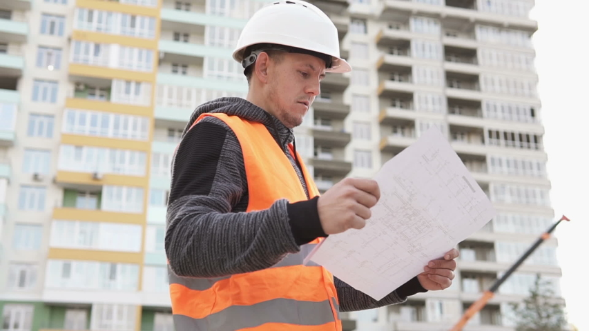 Civil engineer looking drawing of a tall building on the construction site | Shutterstock HD Video #1039039931