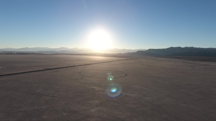 Flying over the Bonneville Salt Flats in Utah by drone, a causeway and car tracks are visible at sunset.