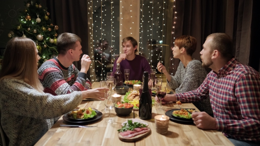 Friends holiday party dinner at home around the table. Celebrate Christmas. Five people eat, drink champagne, talk and laugh. Christmas eve. | Shutterstock HD Video #1039061789
