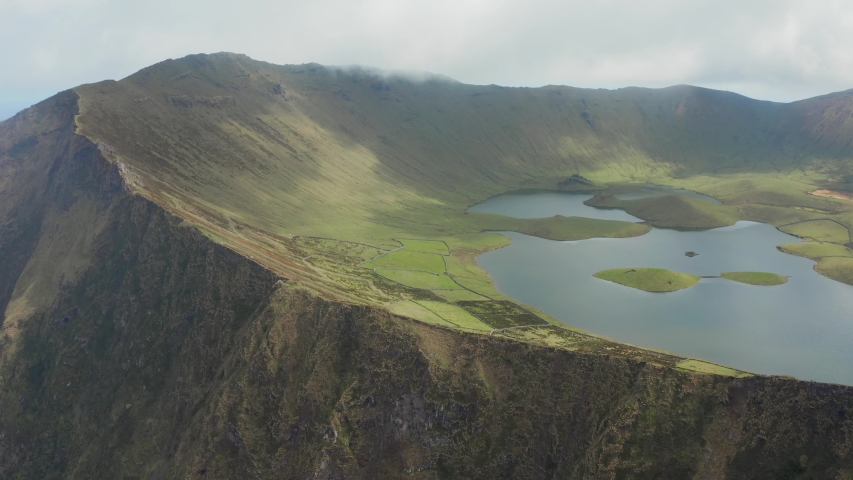 Lake in green lined caldera of huge volcano. Caldeirao top in clouds. Aerial of Corvo, Azores