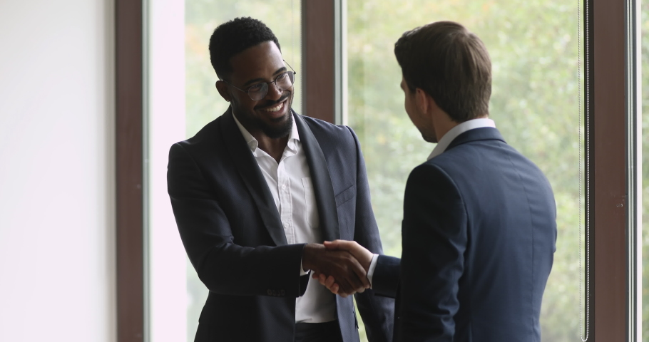 Two happy diverse businessmen talking laughing handshaking standing in office, smiling african and caucasian men executives shake hands at meeting as business agreement, corporate partnership concept Royalty-Free Stock Footage #1039082234