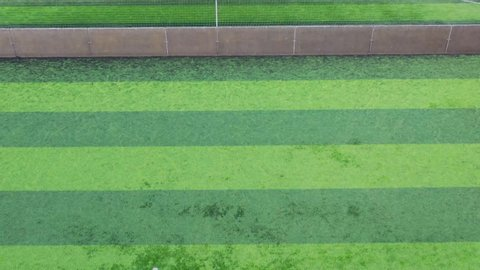 Aerial footage of the drone flying over stripy green football soccer pitches.