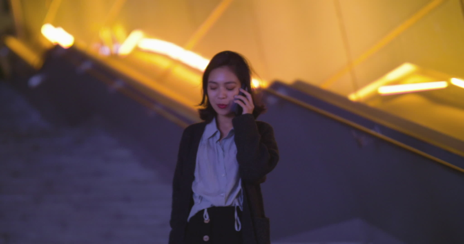 Pretty young asian woman talking on the mobile phone walking in the urban stair street at night slow motion of pretty young Chinese talking on the phone with friends smiling #1039108394