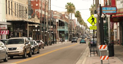 Tampa, Florida - June 14, 2019: People walk along the downtown nightlife of bars and restaurants in historic Ybor City Tampa Florida USA