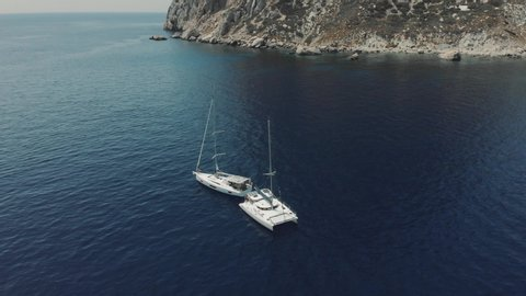 Aerial View of two yachts near Ibiza, es Vedra and Vedranell islands. Drone footage of yachting in the Balearic islands. Unrecognizable people on yachts