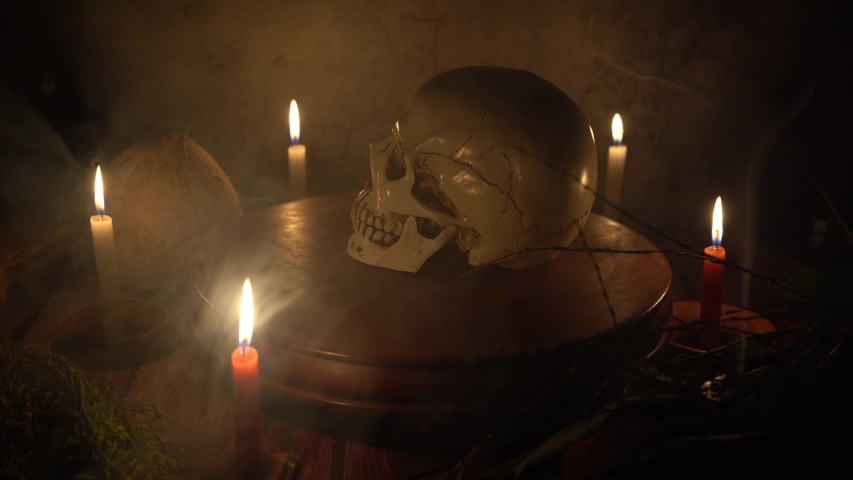 Human skull rotating on a wooden circular platform with dark gray background with candles and mystic herbs around a table with smoke