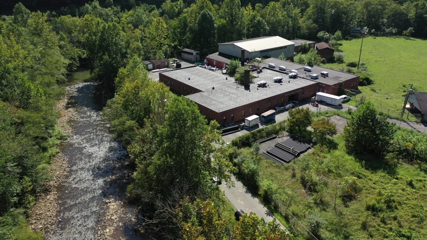 Aerial pull back showing the Marsh Fork Elementary School next to a river with Montcoal mining operation with coal slurry pipelines in mountains of West Virginia.