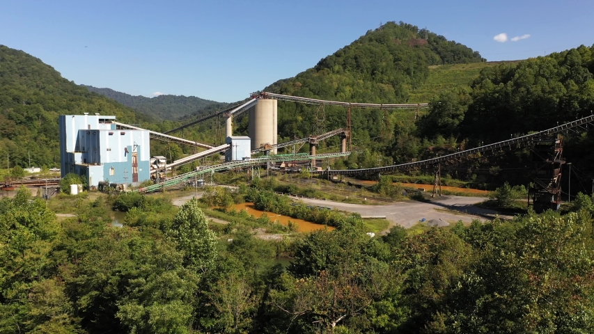 Aerial descent showing the Montcoal mining operation with slurry ponds and coal slurry pipelines in mountains of West Virginia.
