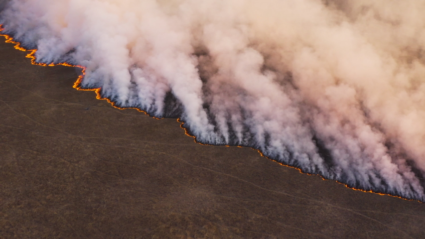Climate emergency.Spectacular high aerial fly over view of a grass fire in the Okavango Delta, caused by drought and climate change, Southern Africa