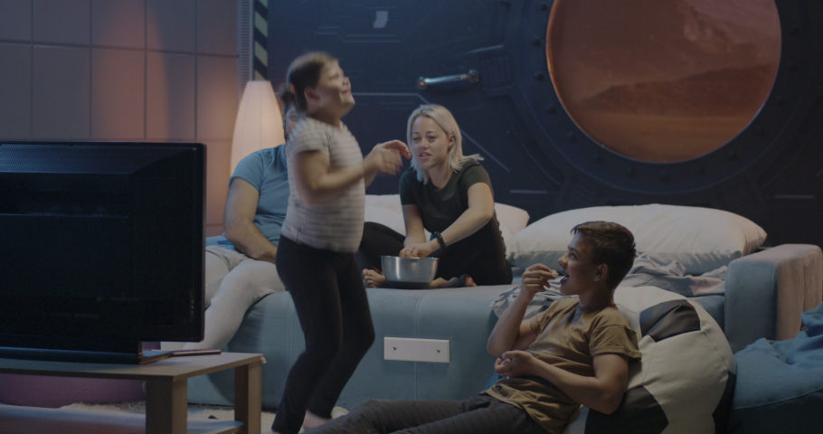 Full shot of a happy family watching television in a Martian base | Shutterstock HD Video #1039139396