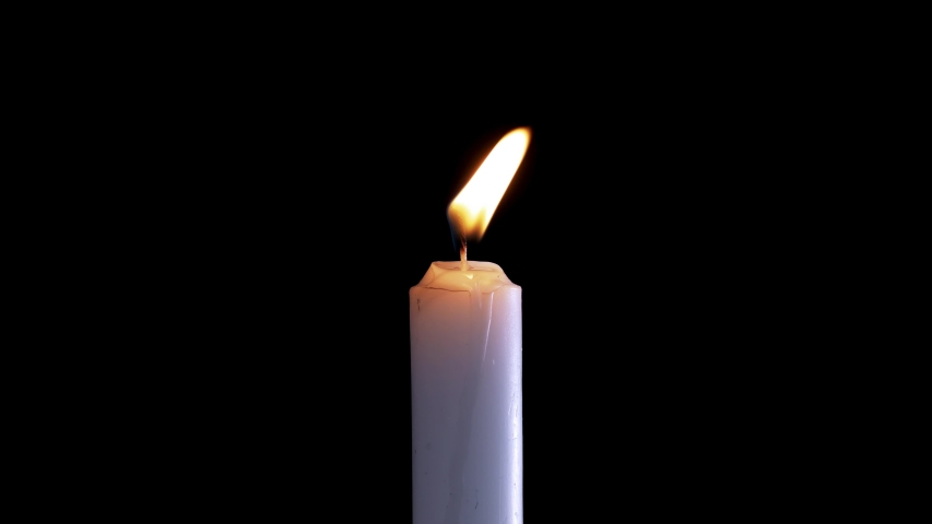 A single white candle burning.Isolated candle burning with dark background.White paraffin candle with yellow shades burns on a black background.Background or illustration of remembrance or celebration