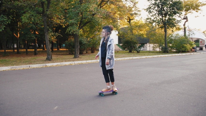 Pretty young woman with dreadlocks riding skateboard in park, slow motion | Shutterstock HD Video #1039141553