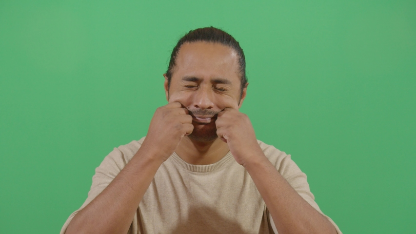 adult man pinching both cheeks studio isolated shot opposite green screen background