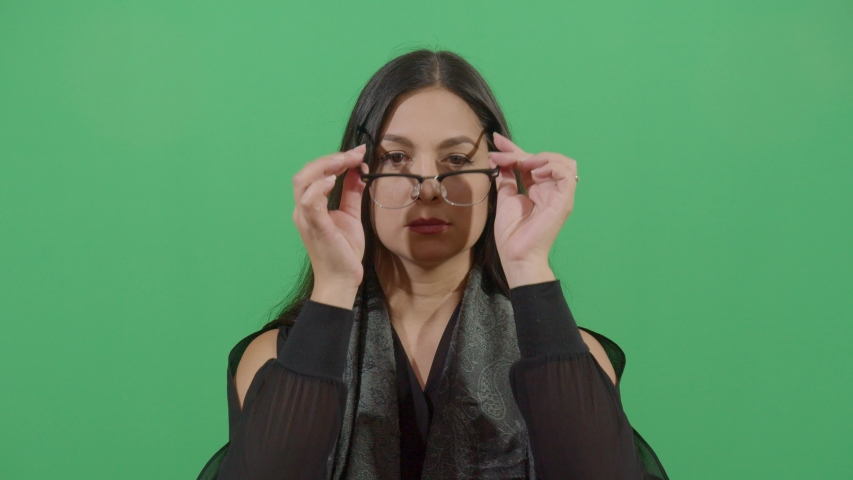 Female putting on prescription glasses taking ready to read something studio isolated shot opposite green screen background | Shutterstock HD Video #1039150952