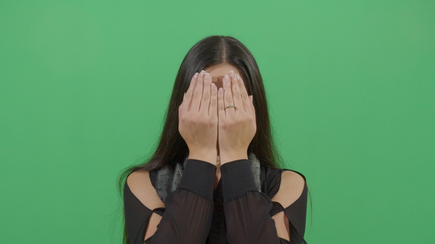 Hands covering the face of a female in the sense that something bad happened or can not look at the viewer studio isolated shot versus green screen background | Shutterstock HD Video #1039151033
