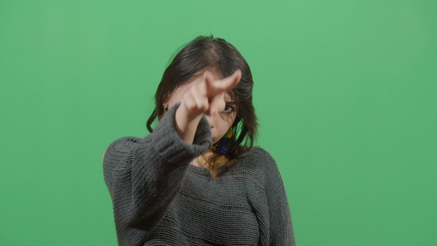 Female making a pose with his fingers like telling the spectator that has a watch on him studio isolated shot versus green screen scene | Shutterstock HD Video #1039151204