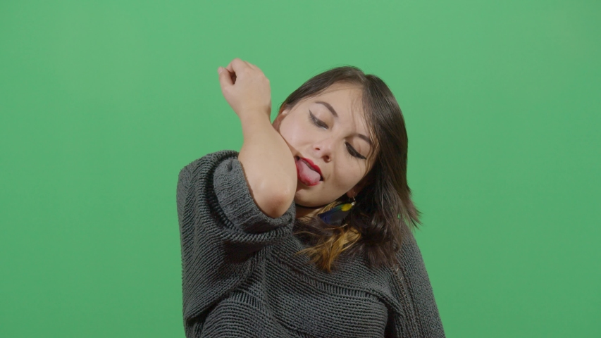 Impossible moves for humans woman trying towards reaching the elbow with the mouth studio isolated shot versus green screen scene | Shutterstock HD Video #1039151324
