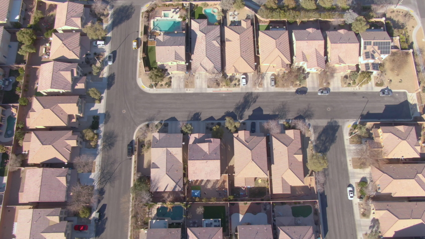 AERIAL TOP DOWN: Flying over terraced houses in a luxury suburban neighborhood in Nevada. Cinematic shot of row houses and backyards in the sunny suburbs of Las Vegas. Empty roads run through suburbia | Shutterstock HD Video #1039160510