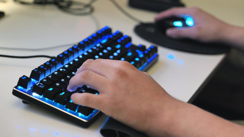 Teenagers hands typing on gaming keyboard. Keyboard keys are backlit. | Shutterstock HD Video #1039162367