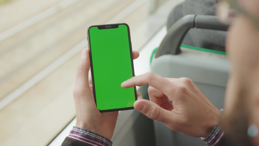 NEW YORK - May 19, 2019: Shot back man young hand uses holding a mobile telephone with a vertical green screen background tram window key smartphone technology touch message display close up | Shutterstock HD Video #1039164275