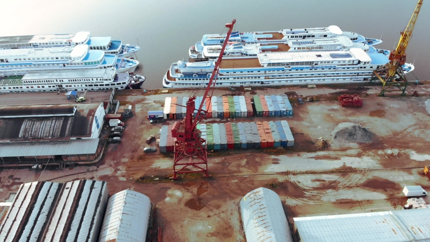 Sea port with ships. A shot from above the river port with ships standing next to each other in the place where containers are loaded by truck cranes