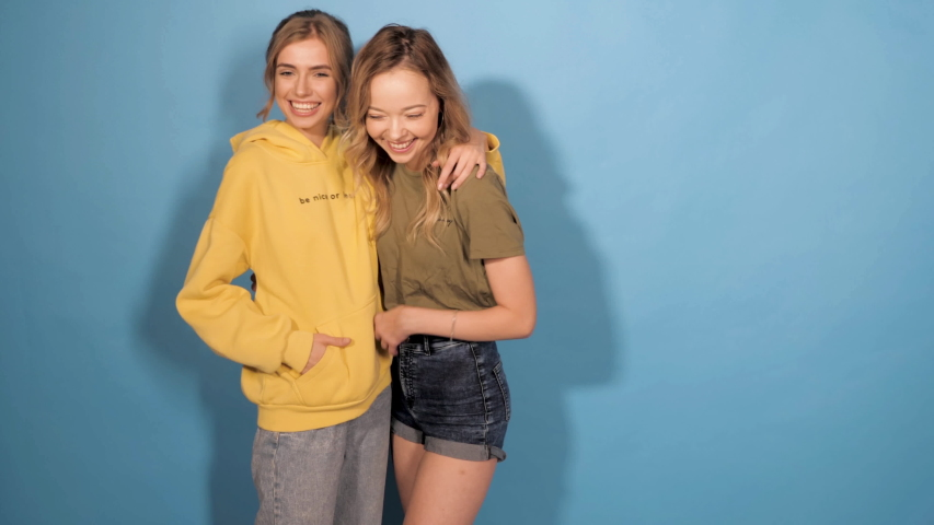 Two young beautiful smiling hipster girls in trendy summer clothes.Sexy carefree women posing in studio near blue wall.Positive models having fun.Showing good relations and hugging.Dancing