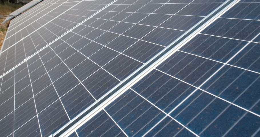 Extreme close up slide camera shot of the panels of small solar power plant mounted on the ground. Alternative energy sources. Ecological production of electricity without environment pollution | Shutterstock HD Video #1039181831