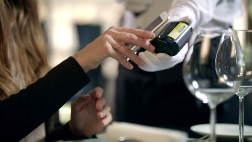 Closeup of female hands paying bill by mobile phone at restaurant. Businesswoman paying for restaurant bill by smartphone. Close up of woman hands making mobile payment in cafe | Shutterstock HD Video #1039183955