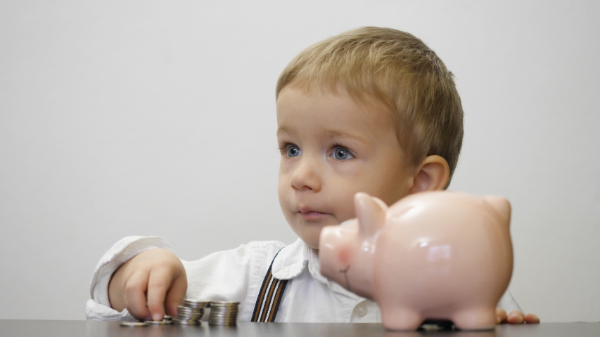 Portrait of child put money in piggy bank, early saving for a safe future | Shutterstock HD Video #1039195907