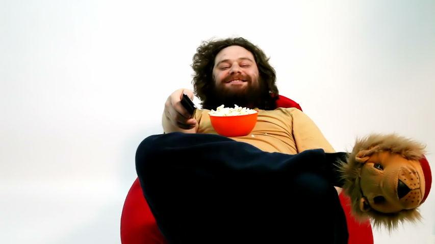A lazy and funny man zapping and eating popcorn in front of TV and cheering. Great concept for creative usage.