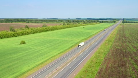 Following a white truck on a freeway on a sunny morning. On both sides of the road, fields with crops separated by forest belts.