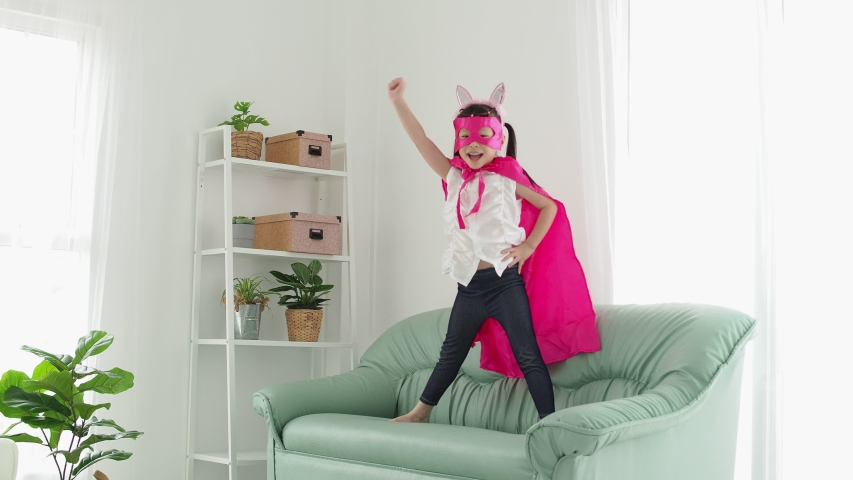 Little asian girl in superhero costume with mask playing in living room    Shutterstock HD Video #1039213715