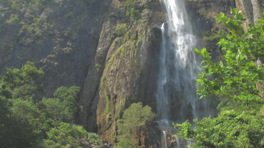 Pictorial large waterfall surrounded by high rocky cliffs and green trees on sunny summer day slow motion. Concept wildlife nature | Shutterstock HD Video #1039226582