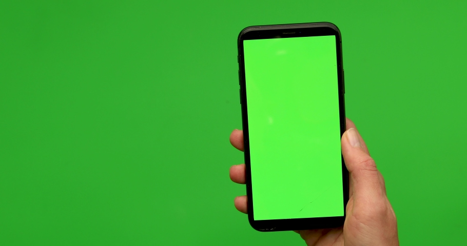 Woman hand holds a smartphone with greeen screen over a green background. Close up footage of hand only | Shutterstock HD Video #1039227350