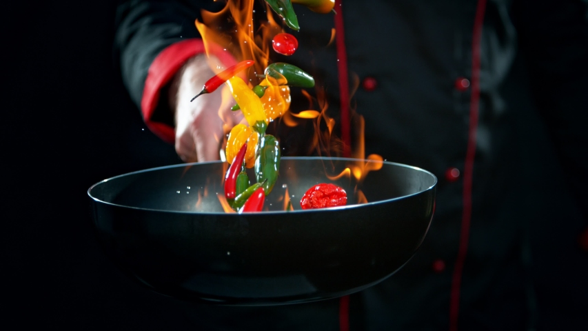 Super Slow Motion Shot of Chef Holding Frying Pan and Falling Chilli Peppers into Fire at 1000fps.